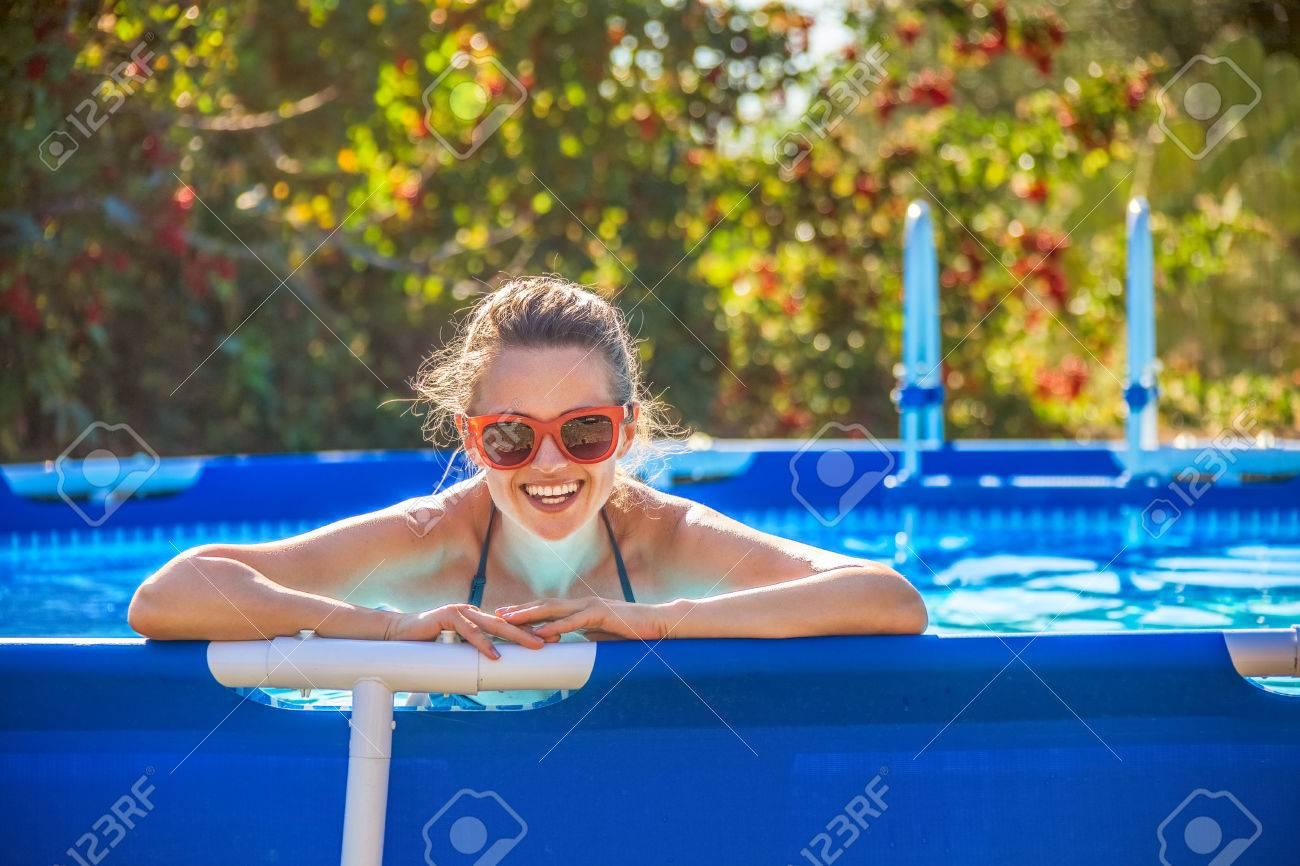 Fun weekend alfresco. Portrait of happy healthy woman in blue beachwear in the swimming pool in sunglasses - 75524549