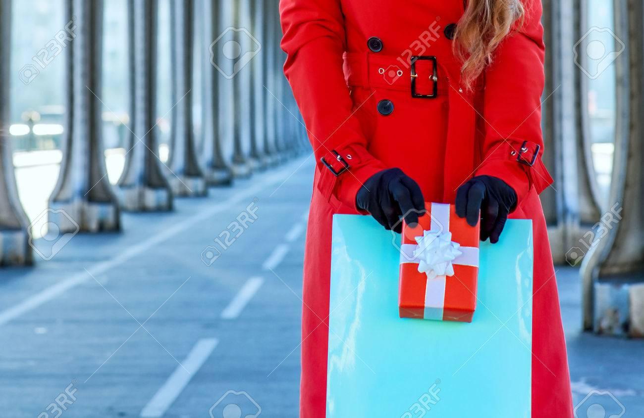 Brillante en París. Retrato de cuerpo entero de mujer elegante turista en gabardina roja en el puente de Pont de Bir Hakeim en París con el bolso de