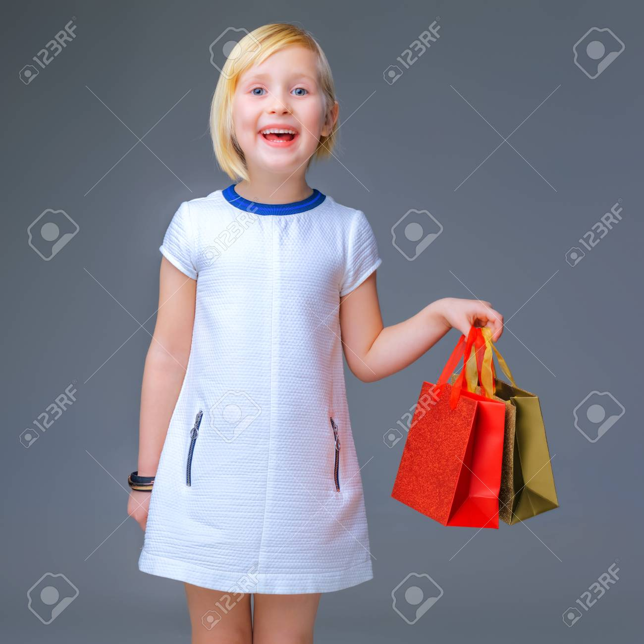 Muchacha Moderna Feliz Niña Moderna En Vestido Blanco Aislado En Gris Mostrando Bolsas De La Compra