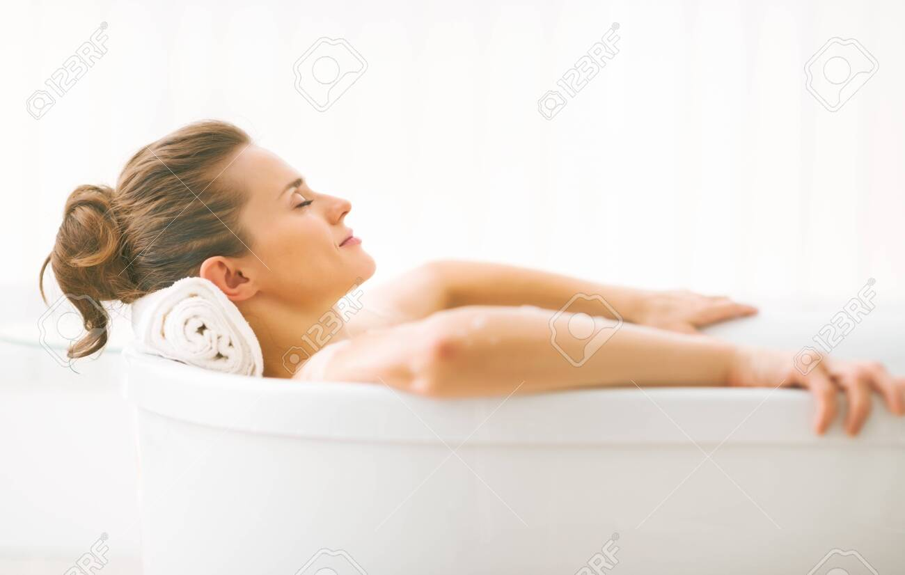 Portrait of young woman relaxing in bathtub - 80681778