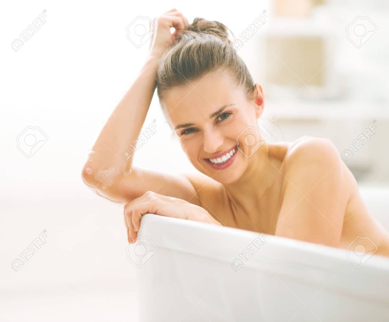 Portrait of smiling young woman in bathtub - 80681552