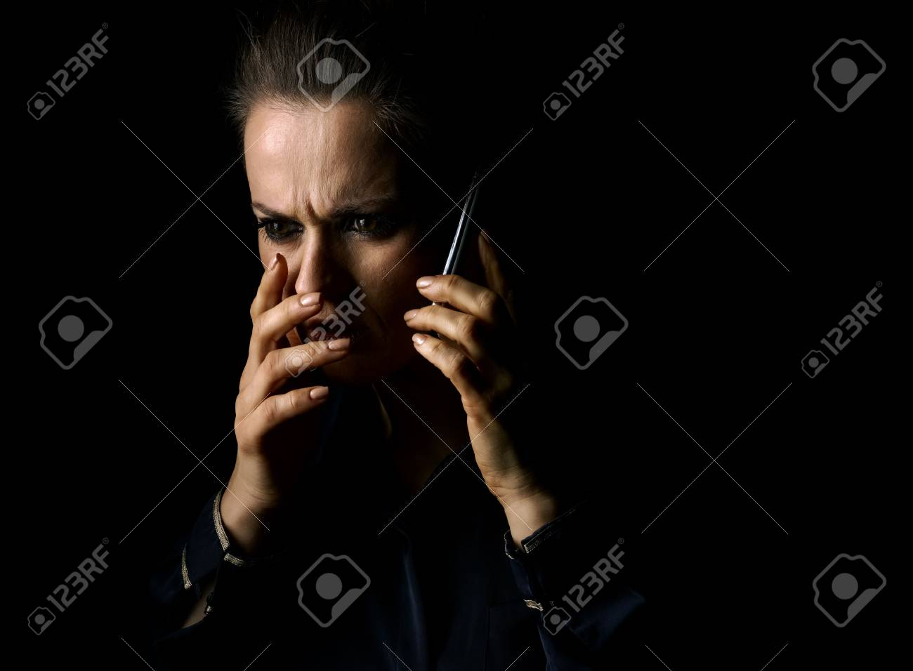 ?oming out into the light. Portrait of stressed woman in the dark dress isolated on black background speaking on a smartphone - 81176993