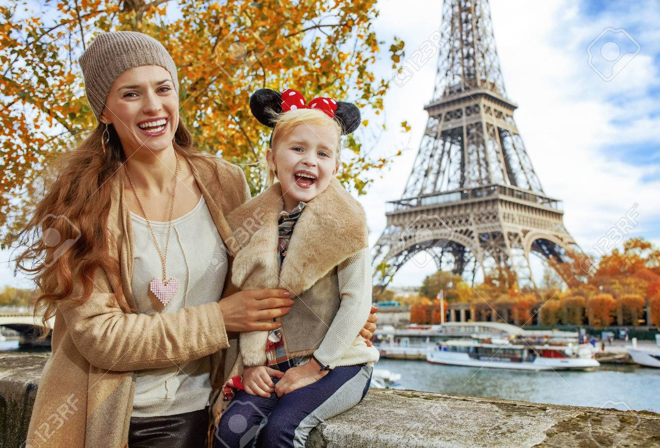 Perfect autumn holidays in Disneyland and Paris. Portrait of smiling tourists mother and daughter in Minnie Mouse Ears on embankment near Eiffel tower in Paris, France sitting on the parapet - 85273175