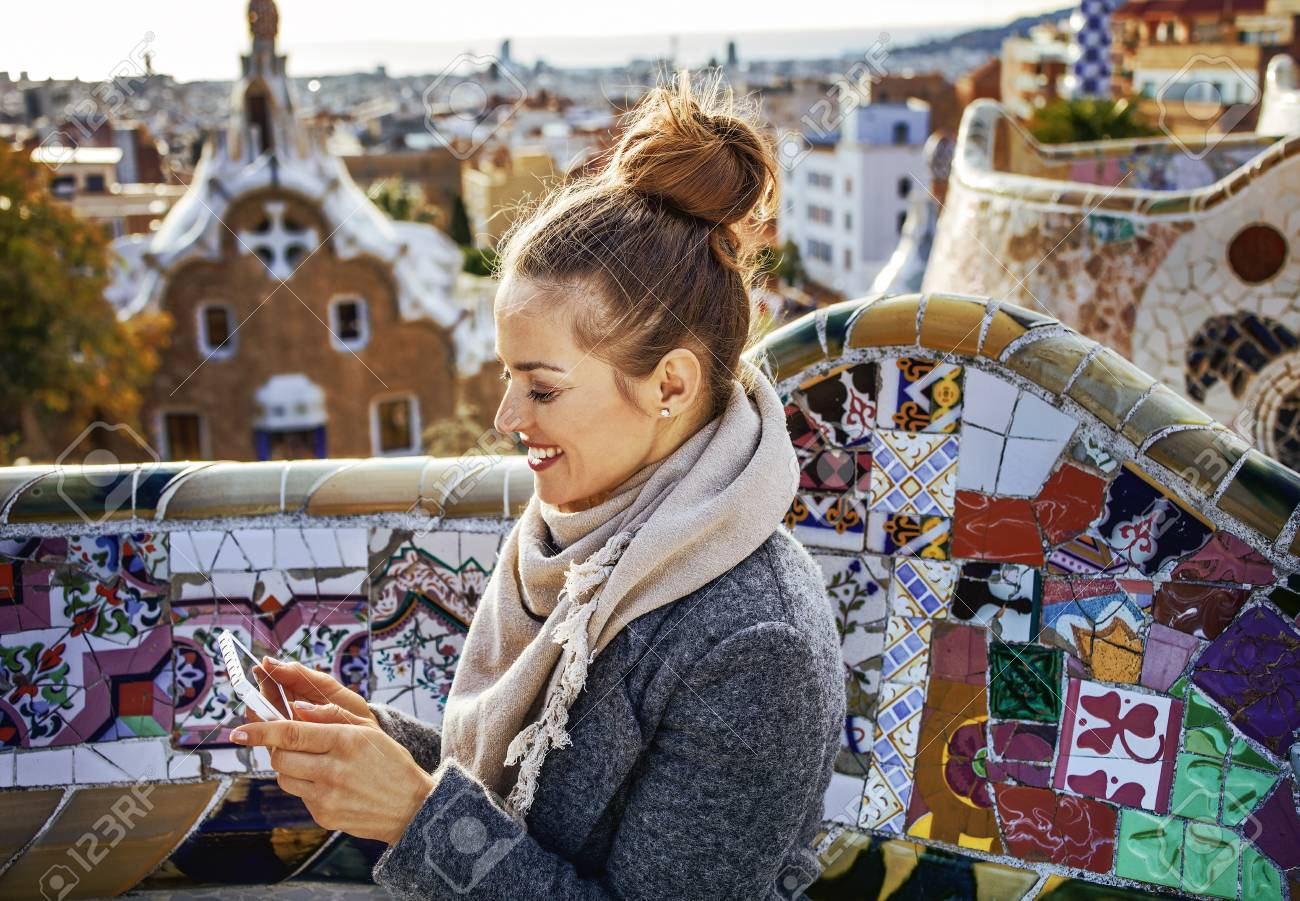 Barcelona signature style. smiling elegant traveller woman in coat at Guell Park in Barcelona, Spain writing sms - 90411393