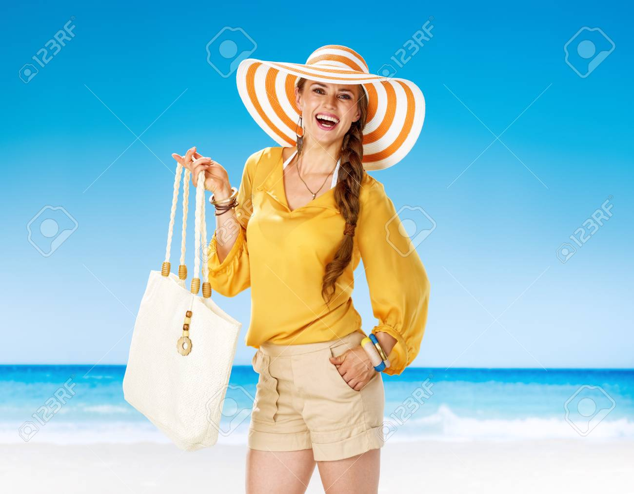 f6c9226b95c Perfect summer. Portrait of happy young woman in shorts and yellow blouse  with white beach