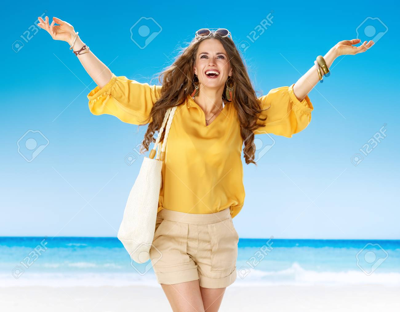 604356a6f28 Perfect summer. happy young woman in shorts and yellow blouse with white  beach bag on