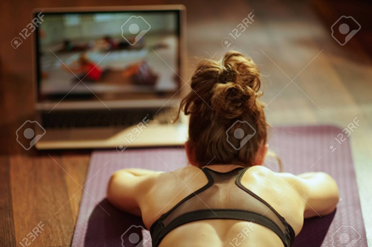 Seen from behind fit sports woman in fitness clothes in the modern living room using online fitness training program in laptop while laying on fitness mat. - 121835140