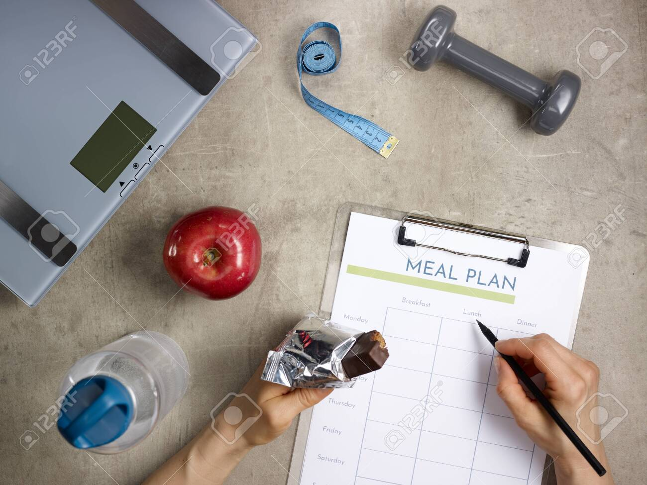 Closeup on weight scales, grey dumbbell, red apple, bottle of water, tape measure laying on the floor and female hands with bitten raw protein bar filling meal plan. - 122620568