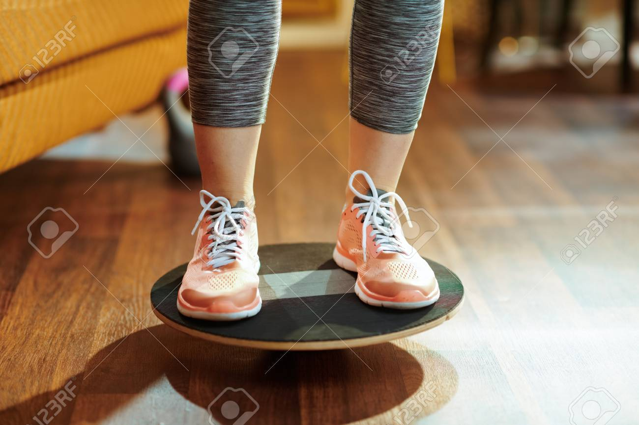 Closeup on fit sports woman in fitness clothes at modern home while training using balance board. - 122822178