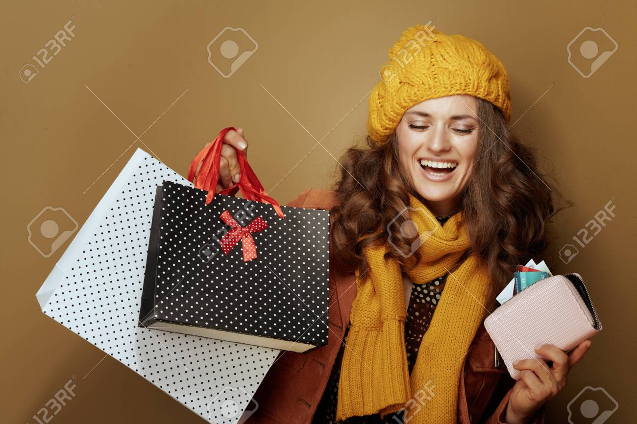 Hello autumn. happy young woman in yellow beret and scarf with credit card, purse and shopping bags isolated on beige. - 129565975