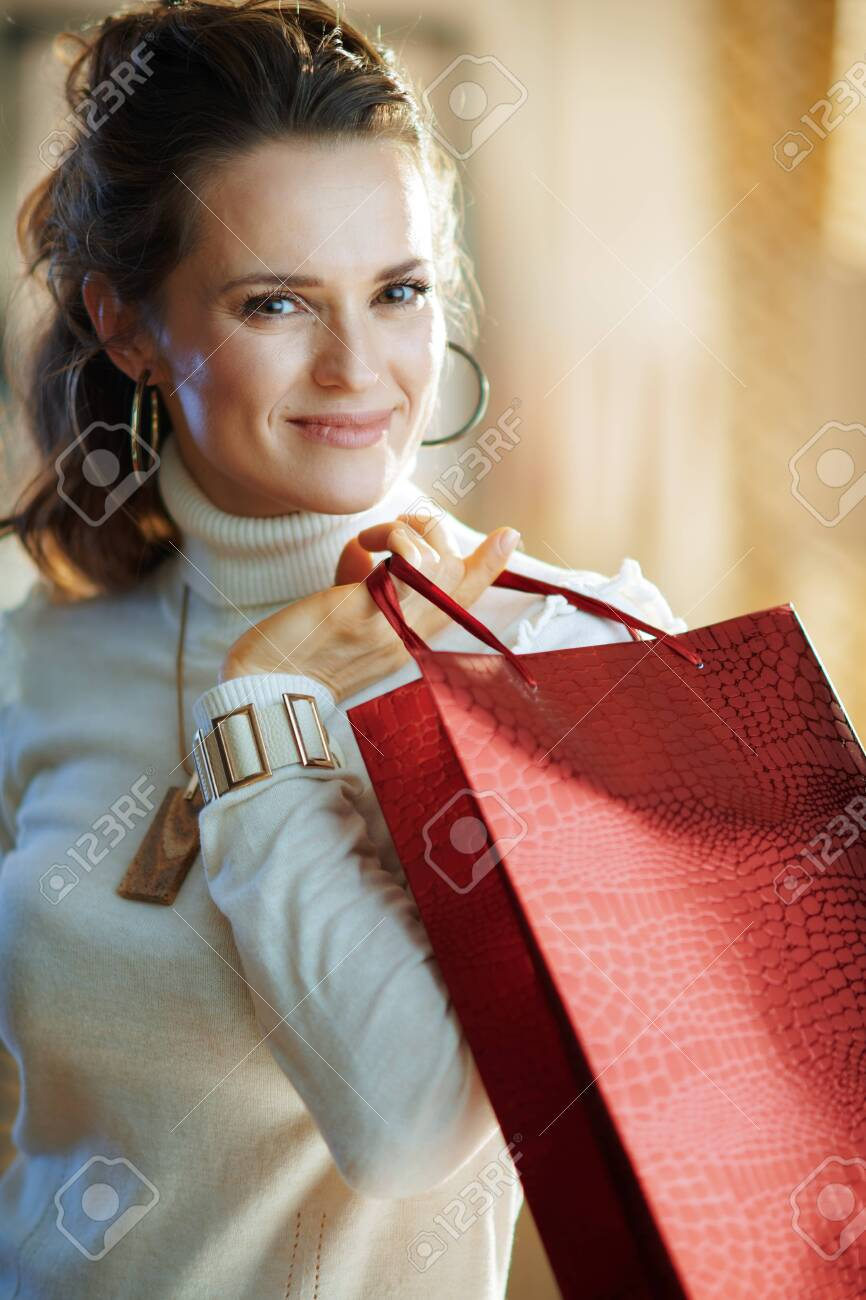 Portrait of elegant female in white sweater and skirt with red shopping bag in the modern house in sunny winter day. - 140598984