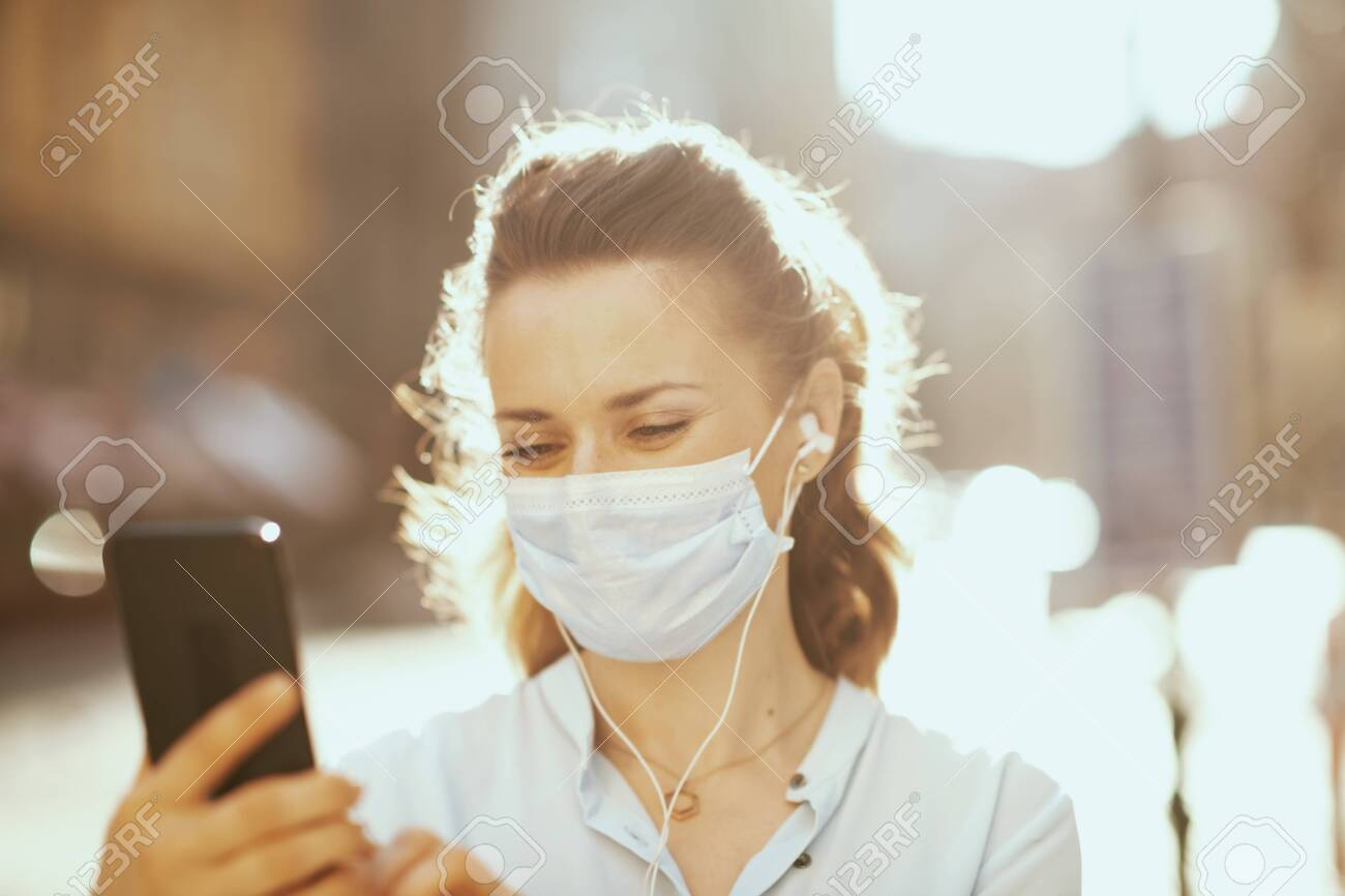 Life during coronavirus pandemic. 40 years old woman in blue blouse with medical mask having virtual meeting outdoors on the city street. - 150508694