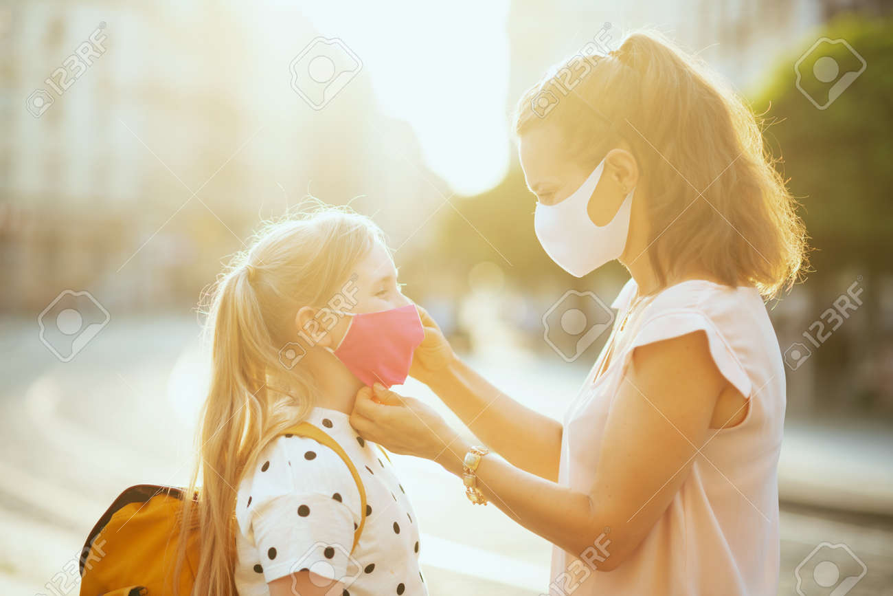 Life during covid-19 pandemic. young mother and child with masks and yellow backpack getting ready for school outside. - 156656181