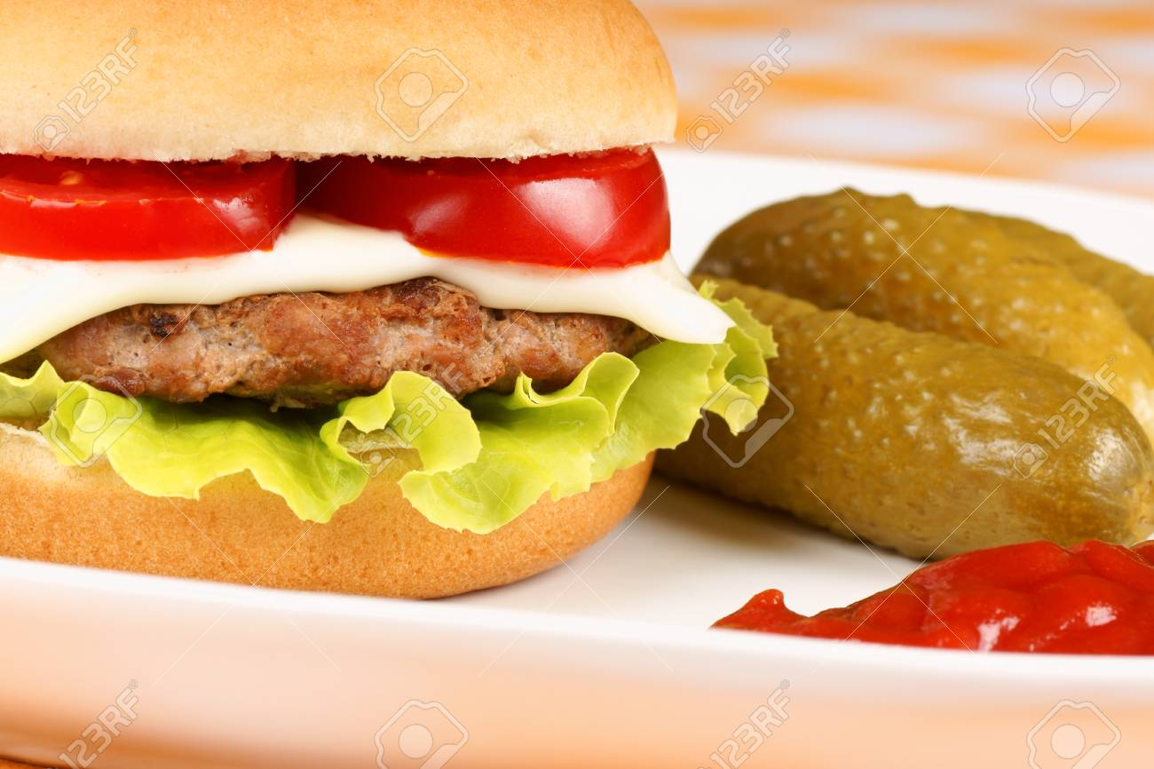 Close-up of a mini cheese burger with pickles and ketchup served