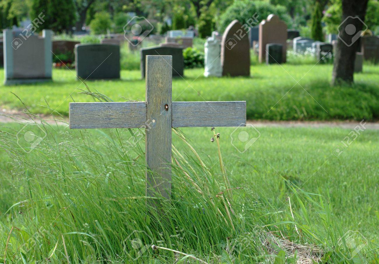 Simple Wooden Cross In An Outdoor Cemetery