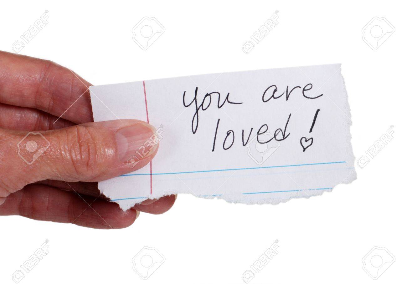 Close up of a hand holding a note with the words: 'You Are Loved'.  Isolated on white. Stock Photo - 15441263
