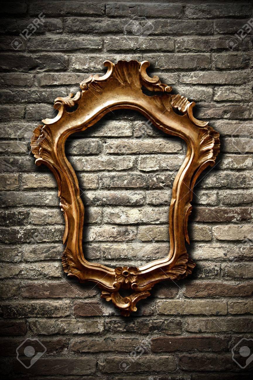A vintage golden frame on a dark brick wall Stock Photo - 8017643