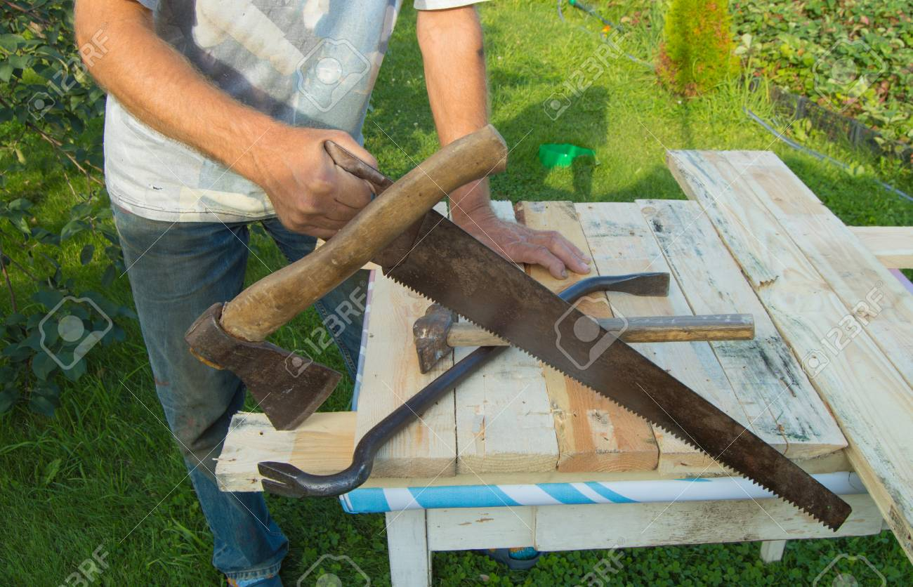 man uses a hacksaw a hatchet a claw hammer for construction