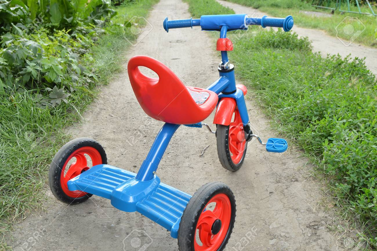 Triciclo Per Bambini In Bicicletta La Bicicletta Blu E Rosso Nuovo è Sulla Strada In Giardino Per Intrattenere I Bambini
