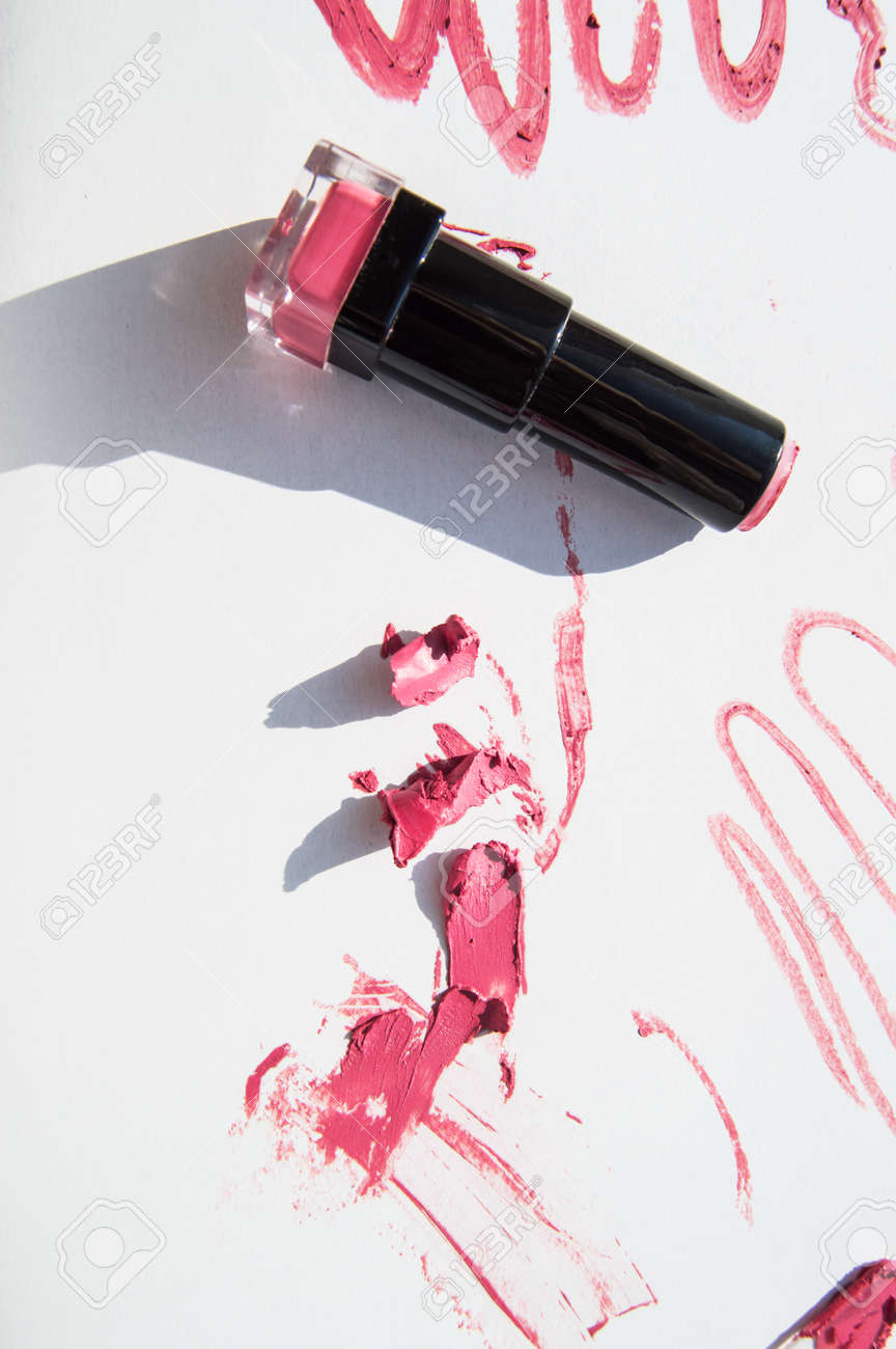 Black used tube of lipstick on a white background, various smudged lines and textures of pink, red lipstick, bright sunlight and shadows, beauty concept. - 168250469