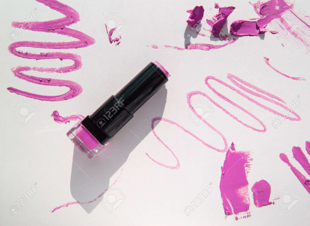 Black used tube of lipstick on a white background, various smudged lines and textures of pink, red lipstick, bright sunlight and shadows, beauty concept - 168250765