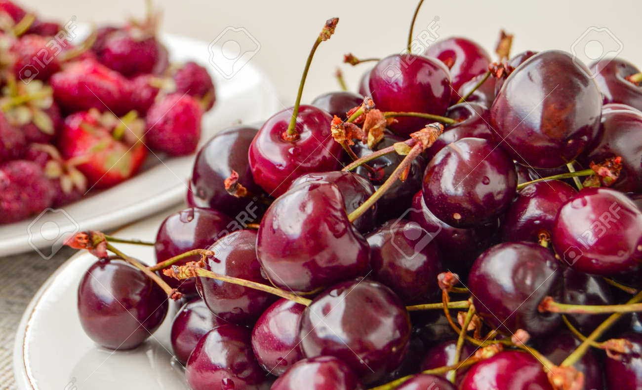 Lots of ripe juicy cherries in a white bowl, summer berry harvest, food background - 169661571