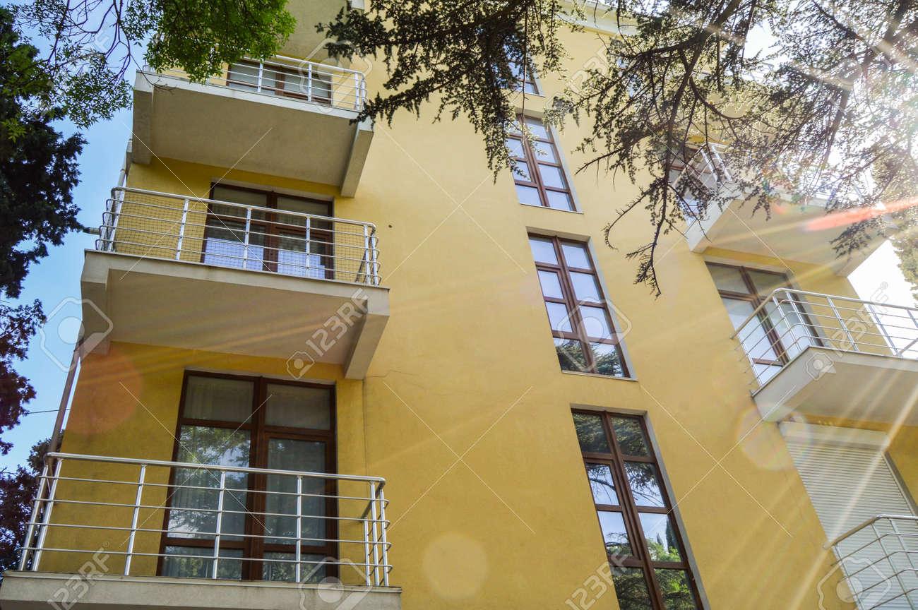 Modern beautiful luxury yellow resort building with balconies, Sunny summer day - 169661596