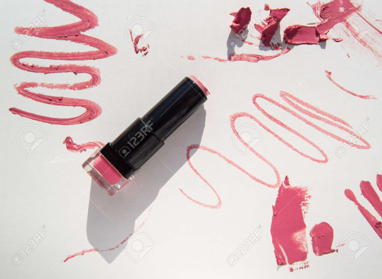 Black used tube of lipstick on a white background, various smudged lines and textures of pink, red lipstick, bright sunlight and shadows, beauty concept - 169661604