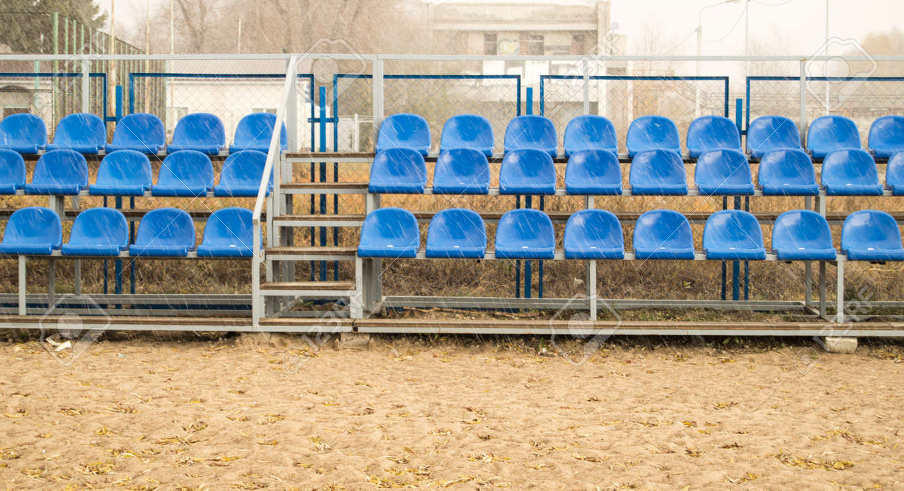 Blue seats on an empty grandstand in an outdoor beach volleyball stadium - 169661608