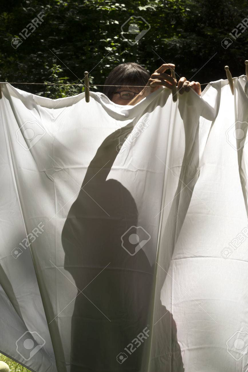 Hanging white bed sheet - A Silhouette Of A Woman Hanging Up A White Bed Sheet On A Washing Line Stock