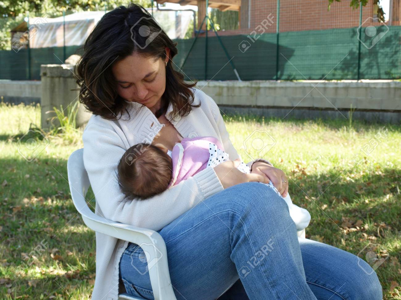 Pretty young brunette mum feeding her baby Stock Photo - 4142484