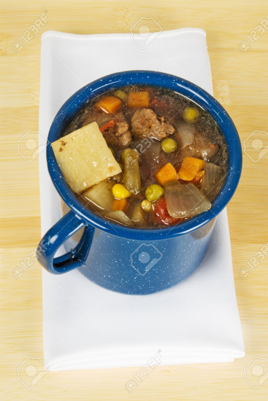 Beef And Vegetable Soup Served In A Blue Tin Cup Ingredients Are Beef Stew Meat