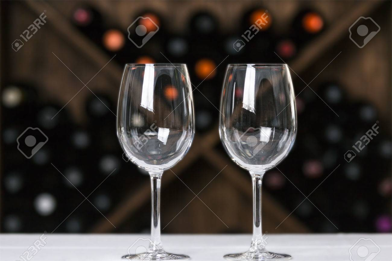Two Empty Wine Glasses On A Table On A Wooden Wine Rack Background