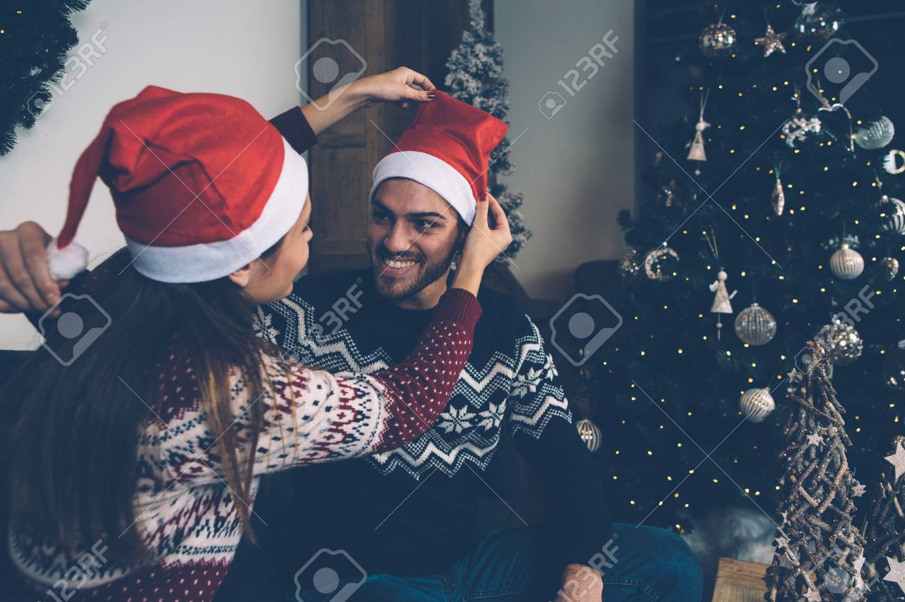 4124568b1 Laughing loving couple in sweaters trying on Santa hats in room..