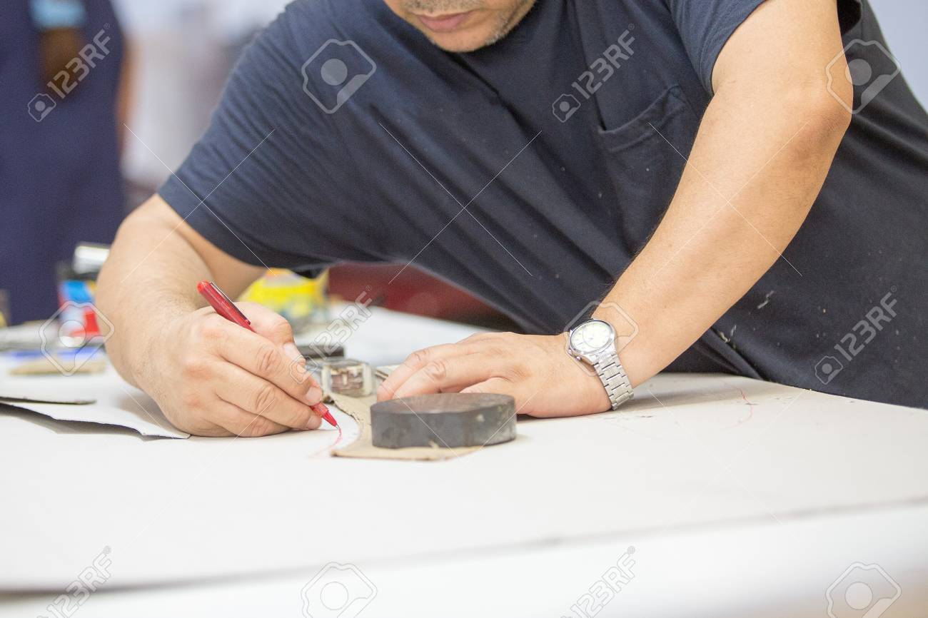 Close up of a male worker working with the pattern of the leather in the work table to upholstering the interior car components in a leather upholstery factory - 106481845