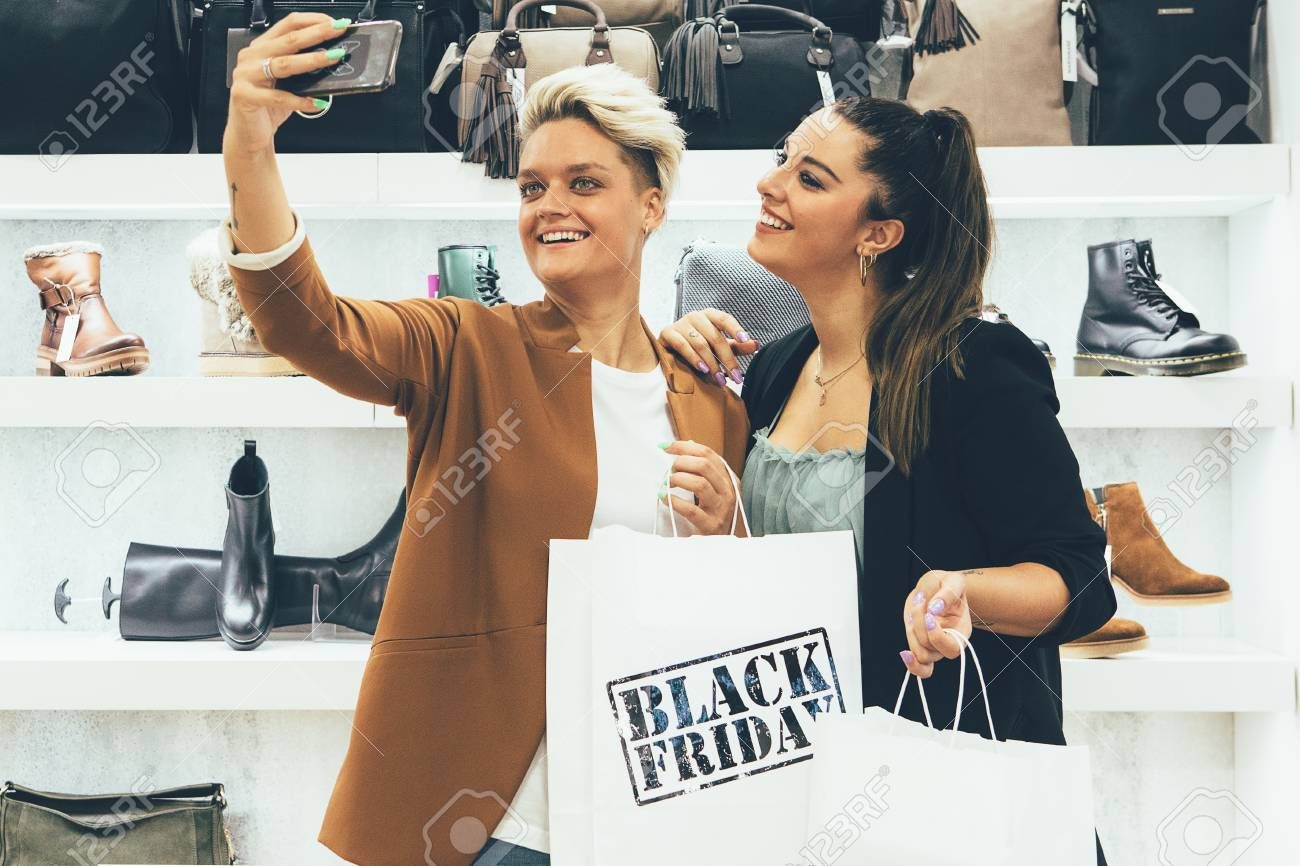 ad5271816873 Black Friday. Smiling couple of female shoppers holding paper shopping bags  are taking a selfie