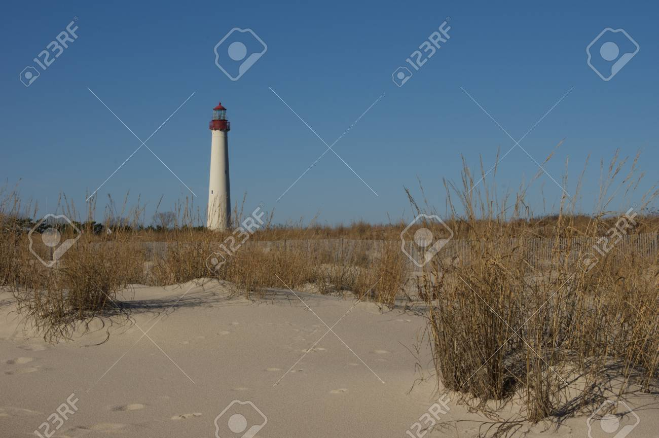 A sandy beach with a lighthouse in the background. - 35102844