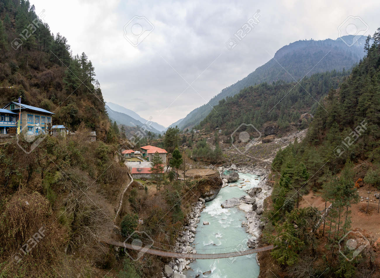 A small mountain town beside a river and swinging bridge in the mountains of Nepal. - 169836049