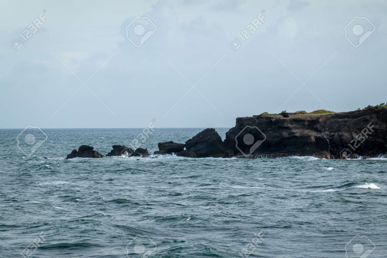 A rocky peninsula jutting out into the sea. - 171189489