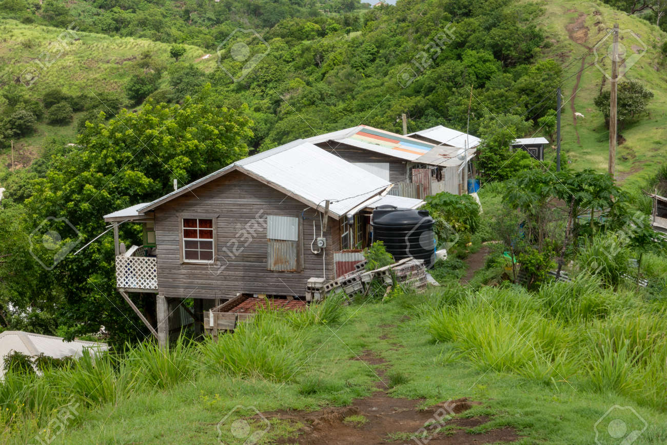 A house perched on the side of a hill in Grenada. - 171189952