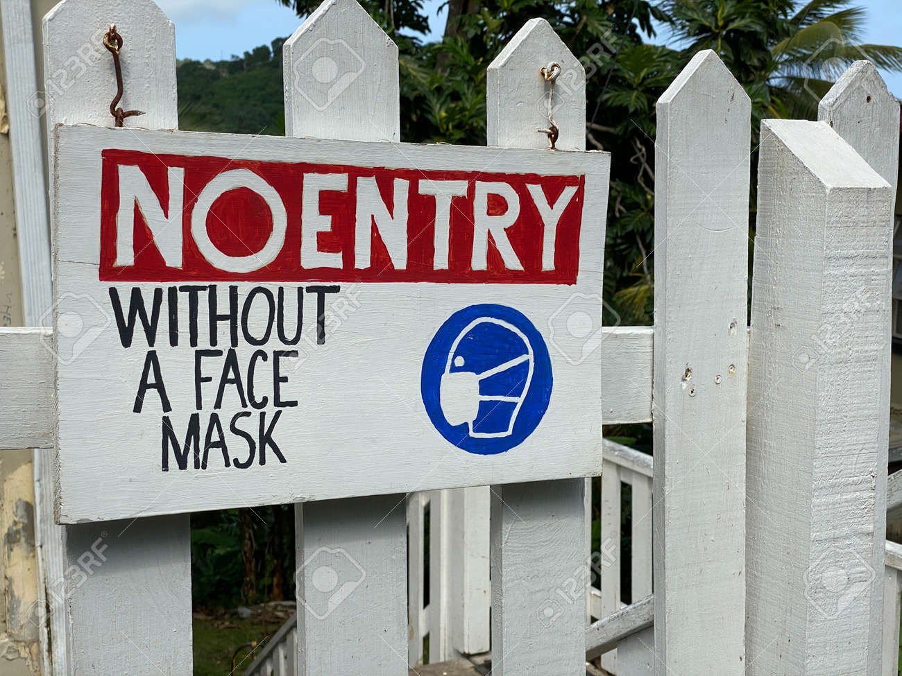 A No Entry Without Face Mask Sign on a fence. - 171244909