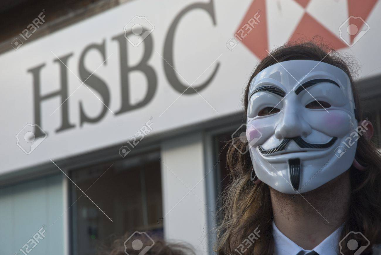 Occupy Exeter activist wearing a Guy Fawkes mask campaigning outside the Exeter branch of HSBC bank Stock Photo - 12272123
