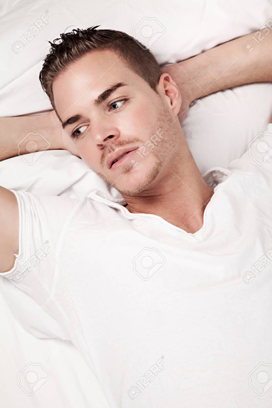 beautiful young man lying in bed Stock Photo - 19564320