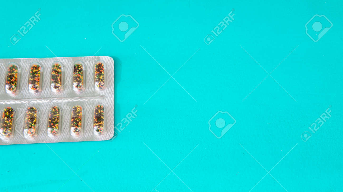 Flat lay view of a plastic blister with colorful pills placed on top of a cyan wooden surface with negative space - 168497316