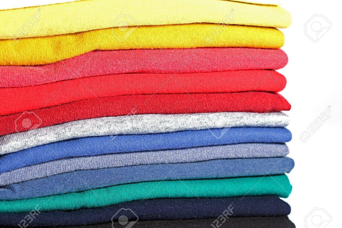 Stack of colored tee shirts on a shelf - 5575035