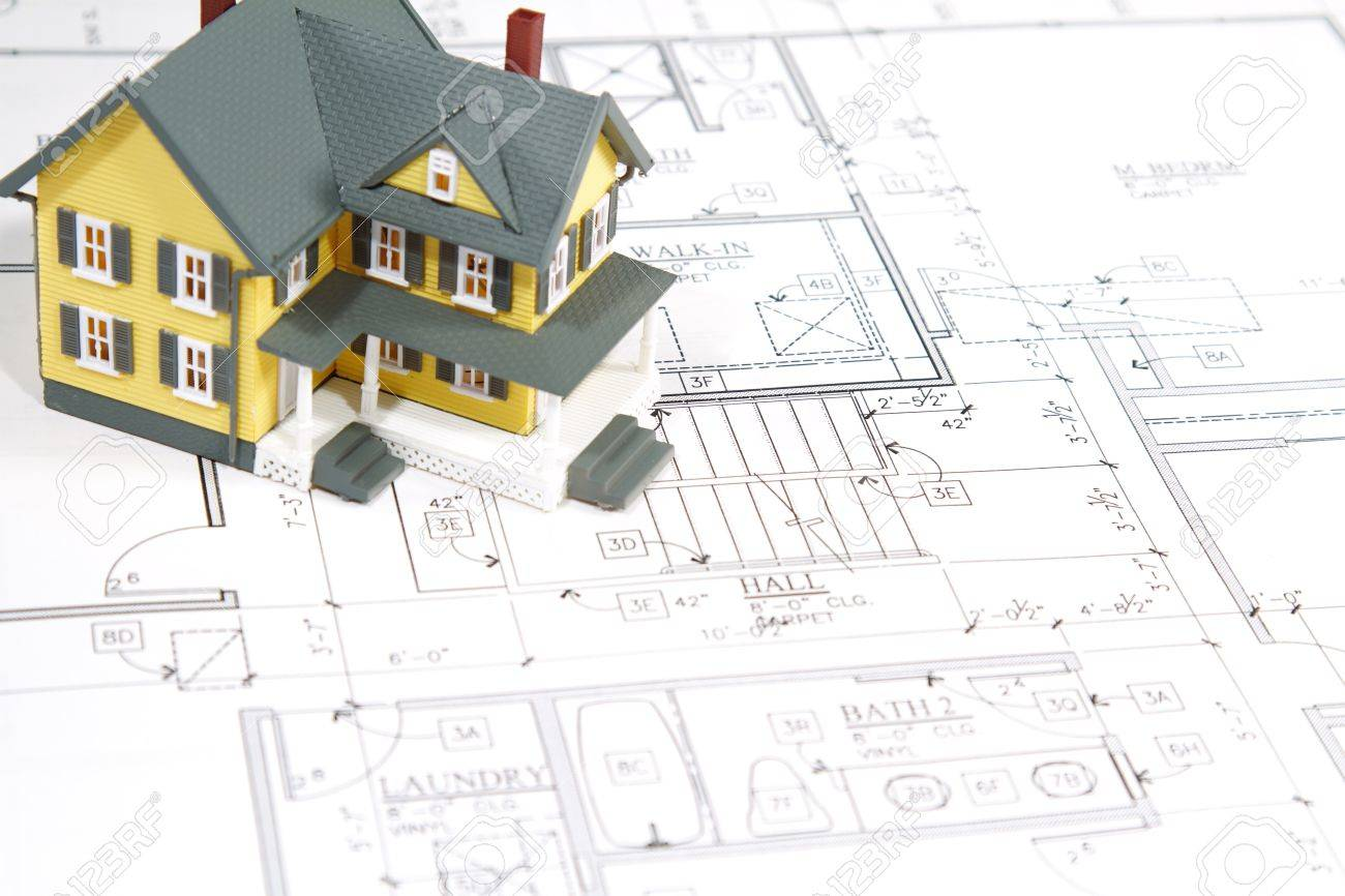 stock photo residential home blueprints with a hand made house model