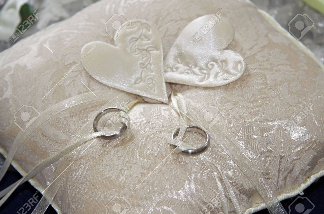 Two wedding rings on a beige pillow Stock Photo - 8743305