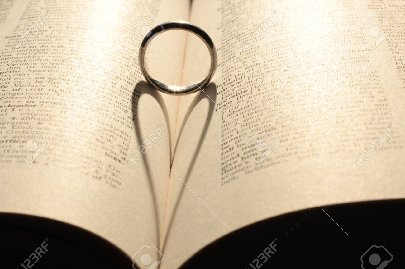 Heart Shadow From Wedding Ring On Book Stock Photo Picture And