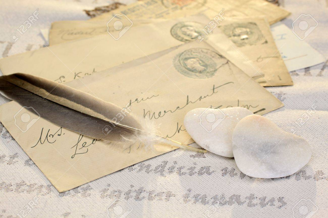 Two stone hearts with feather and old letters Stock Photo - 12638292