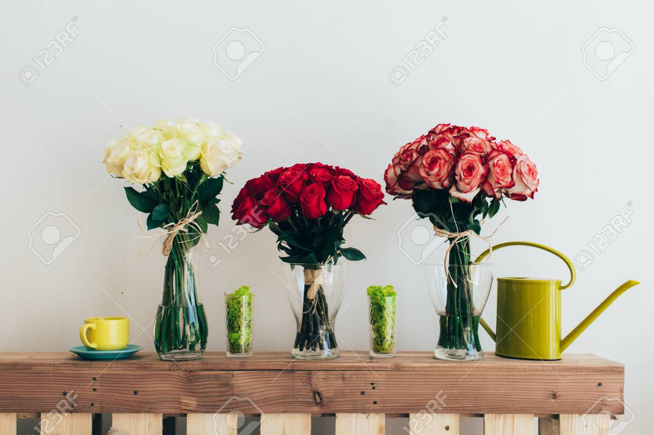 Bouquets of roses in three glass vases next to a watering can bouquets of roses in three glass vases next to a watering can on a white wall reviewsmspy